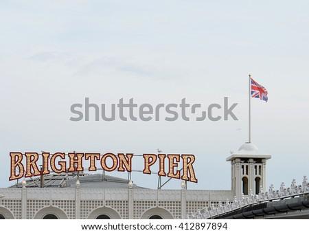 Brighton Pier Signage with Union Jack Flying - stock photo