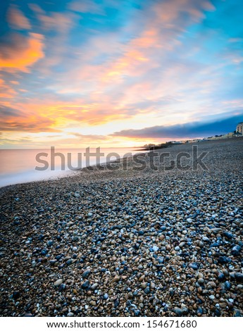 Brighton's pebbly beach at sunset - stock photo