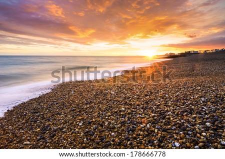Brighton's pebbly beach at sunset - stock photo