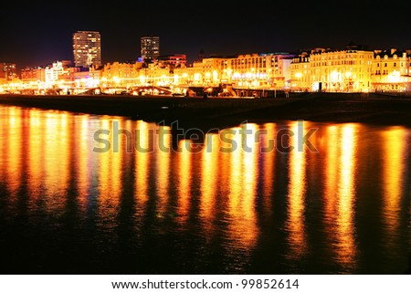 Brighton seafront at night, city lights reflecting in sea along coastline - stock photo