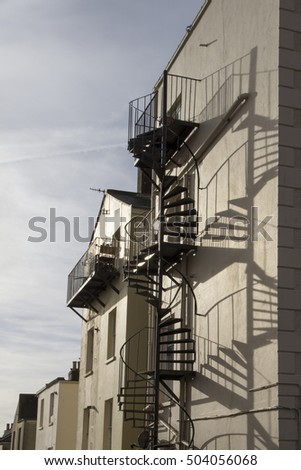 BRIGHTON, SUSSEX UK 13 October 2016: Old fashioned external stairs fire escape on the rear of an old style white industrial or office building in Brighton.