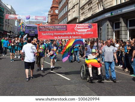 BRIGHTON, UK - AUG 13. Pink Punters Nightclub, a supporting group of the LGBT community join the pride parade with Rainbow Operation banner at Brighton & Hove Pride Festival on August 13, 2011. - stock photo