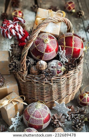 Brights Christmas Toys with gifts. Basket, Red balls, Pine cones, Boxes, Walnuts, Snowflakes, Sweet Candies on Wooden Table. Vintage style - stock photo