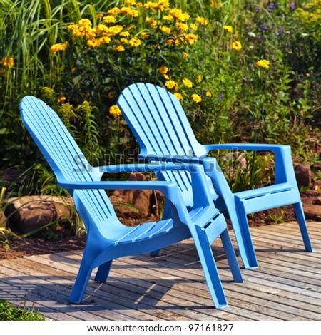 Brilliant blue plastic outdoor Adirondack chairs on the deck in a summer garden. - stock photo