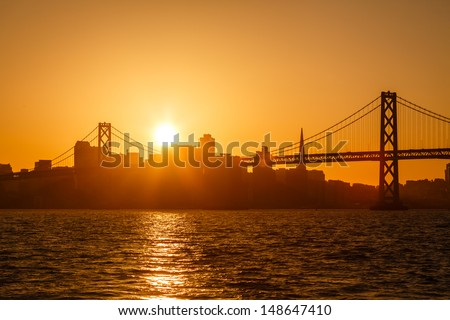 Brilliant golden glow back lights San Francisco skyline and and reflects on the water under the Bay Bridge