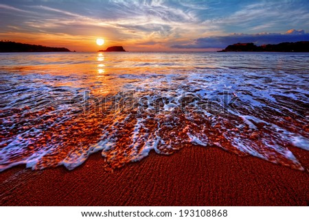 Brilliant ocean bay sandy beach sunrise with distant cliffs - stock photo