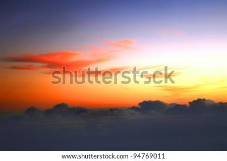 Brilliant orange skies hide above cloud line on flight between Kauai and the Big Island of Hawaii. - stock photo