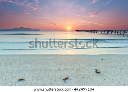 Brilliant sunrise on a sea pier with azure waters