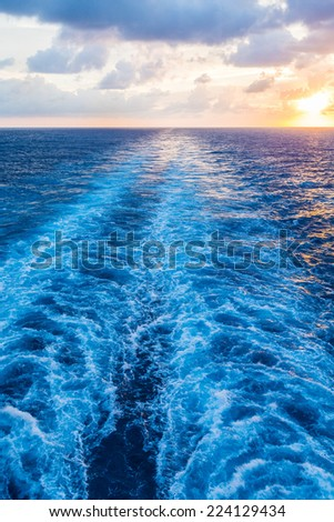 Brilliant sunset in the wake of a cruise ship at sea - stock photo