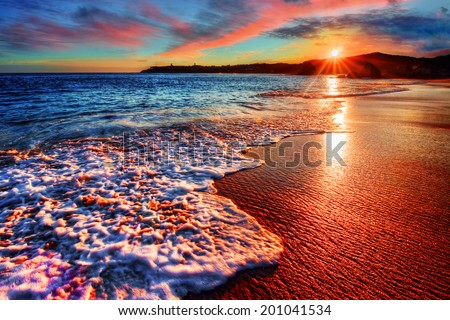 Brilliant vacation destination beach sunrise with colorful sand bright sea foam pink clouds and distant cliffs - stock photo