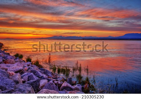 Brilliantly red river sunset with distant mountains and colorful clouds - stock photo