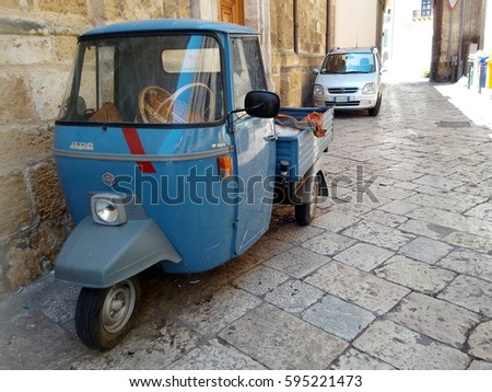 BRINDISI, ITALY - JULY 14, 2016: A typically Italian three wheeled vehicle Piaggio Ape P501 filled with woven baskets parked on a street in Brindisi, southern Italy.