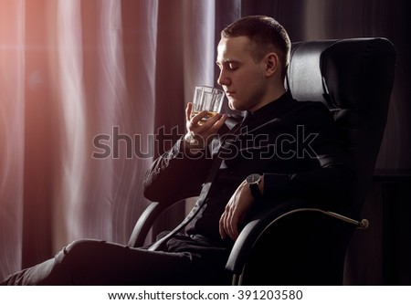 bring down stress. Young handsome stressed businessman in formal wear taking off his necktie holding a glass of whiskey in his hand. Isolated on black background. - stock photo