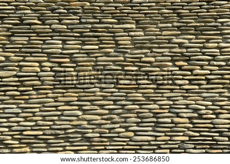 Bringing natural stone tiles for a pattern lock on a brick wall. - stock photo