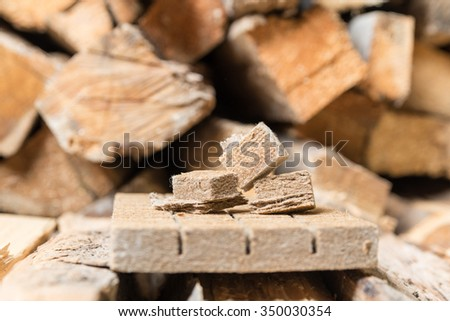 Briquettes for firing, ignition on the background of wood. View from side - stock photo