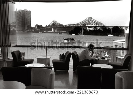 BRISBANE, AUS - SEP 25 2014:A businessman dining in restaurant at Eagle Street Pier.It is an iconic waterfront precinct with world class dining options and unrivaled views of the Brisbane River. - stock photo