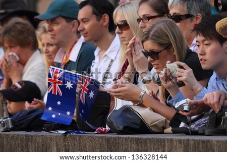 BRISBANE, AUSTRALIA - APRIL 25 : Flag waving crowds line the march route during Anzac day commemorations  April 25, 2013 in Brisbane, Australia - stock photo