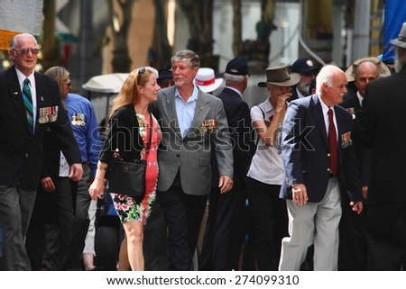 BRISBANE, AUSTRALIA - APRIL 25 : VCouple embrace whilst marching during Anzac day centenary commemorations April 25, 2015 in Brisbane, Australia - stock photo