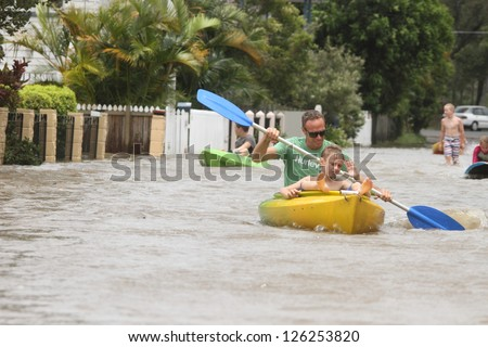 BRISBANE, AUSTRALIA - JANUARY 28 : Unidentified residents taking canoe rides in flooded street from ex tropical cyclone Oswald on January 28, 2013 in Brisbane, Australia - stock photo