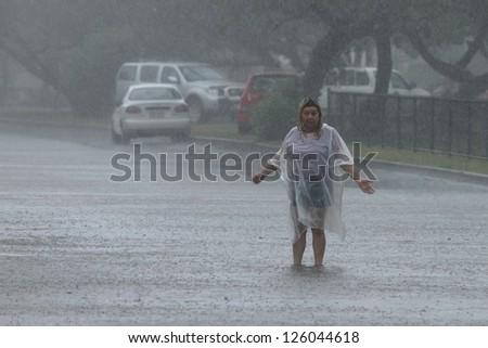 BRISBANE, AUSTRALIA - JANUARY 27 : Unidentified woman sings in the rain during ex tropical cyclone Oswald on January 27, 2013 in Brisbane, Australia - stock photo