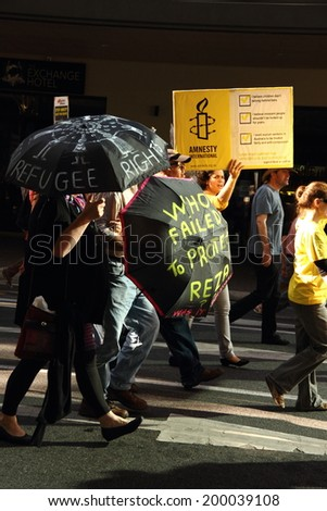 BRISBANE, AUSTRALIA - JUNE 22 : Anti governement  immigration policy protesters marching streets during World Refugee Rally June 22, 2014 in Brisbane, Australia - stock photo