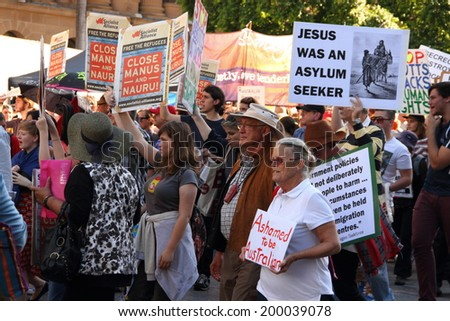 BRISBANE, AUSTRALIA - JUNE 22 : Anti government  immigration policy protesters marching streets during World Refugee Rally June 22, 2014 in Brisbane, Australia - stock photo