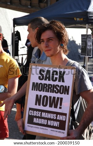 BRISBANE, AUSTRALIA - JUNE 22 : Unidentified protester with sign to sack immigration minister at World Refugee Rally June 22, 2014 in Brisbane, Australia - stock photo