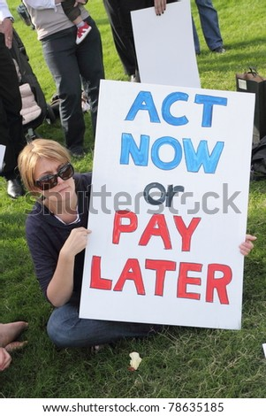 BRISBANE, AUSTRALIA - JUNE 6 : Woman with act now or pay later anti pollution sign at say Yes to carbon tax World Environment Day protest 6, 2011 in Brisbane, Australia - stock photo
