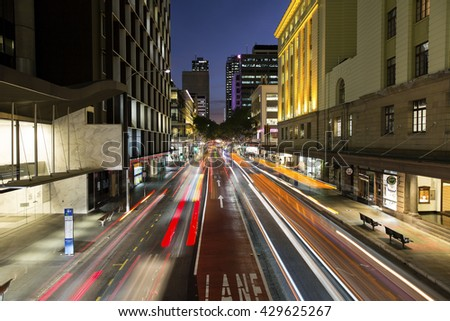 BRISBANE, AUSTRALIA - MAY 25 2016: Brisbane CBD night life and traffic light trails, at the intersection of Adelaide and Edward streets.