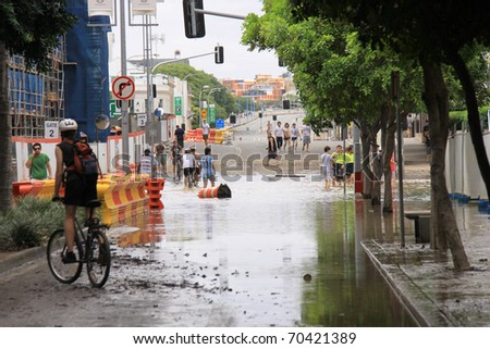 BRISBANE, QUEENSLAND/AUSTRALIA - JANUARY 13: Flooded street with bicycle driver on January 13, 2011 in South Bank, Brisbane, Queensland, Australia. - stock photo