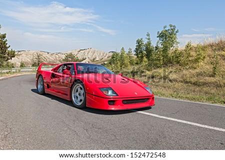 "BRISIGHELLA, RA, ITALY  - AUGUST 31: unidentified driver on a italian sports car Ferrari F40 at rally ""Trofeo Lorenzo Bandini"" on August 31, 2013 in Brisighella, RA, Italy  - stock photo"
