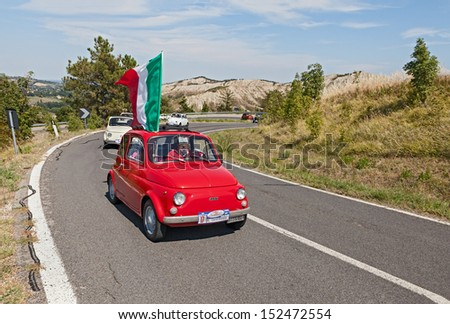 "BRISIGHELLA, RA, ITALY  - AUGUST 31: unidentified driver on a vintage small car Fiat 500, with italian flag, at rally ""Trofeo Lorenzo Bandini"" on August 31, 2013 in Brisighella, RA, Italy"