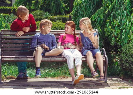 Brisk conversation.  Pleasant vivacious smiling  friends talking and looking at each other while sitting on the bench. - stock photo