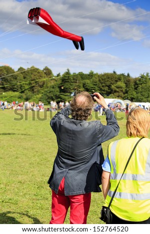 BRISTOL - AUGUST 31: Bristol's elected mayor, George Ferguson takes a photograph of his specially commissioned red trouser kite at the Bristol International Kite Festival, England, August 31, 2013  - stock photo