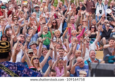 BRISTOL, ENGLAND - JULY 21: An audience shows its appreciation for an act at the 41st  Harbour Festival at Bristol, England on July 21, 2012. A record 300,000 people attended the event over three days - stock photo