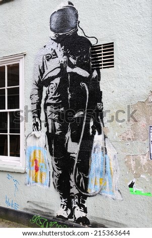 BRISTOL - MAR 17: View of a spaceman themed graffiti piece by Banksy on a wall in the city centre on Mar 17, 2011 in Bristol, UK. Bristol is internationally renowned for its vibrant street art scene. - stock photo