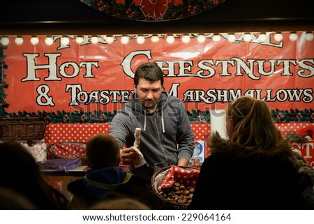 BRISTOL - NOV 7: A food vendor serves at a Christmas market in the city centre on Nov 7, 2014 in Bristol, UK. Broadmead shopping district is home numerous market stalls during the holiday season.  - stock photo