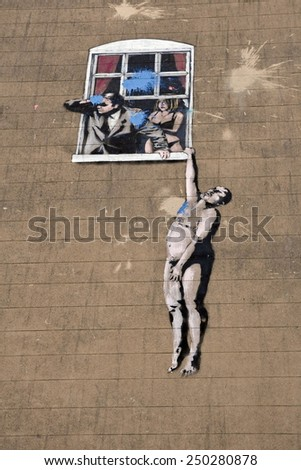 BRISTOL - SEP 26: View of a Banksy graffiti piece titled Naked Man on a building in the city centre on Sep 26, 2010 in Bristol, UK. Banksy is an internationally renowned street artist from Bristol. - stock photo