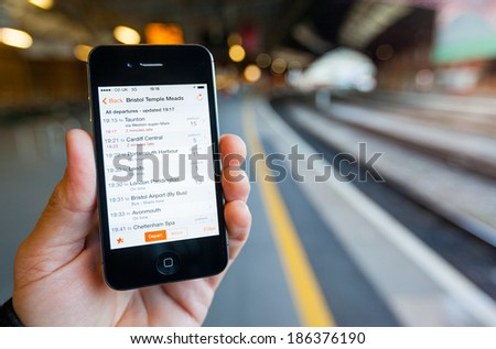 BRISTOL, UK - APRIL 8, 2014: A male hand holding an iPhone 4s at Bristol Temple Meads railway station. The smart phone displays live train travel information on the Train Times App. - stock photo