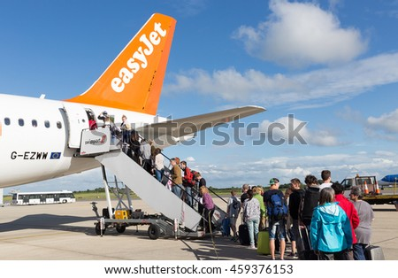 BRISTOL, UK - JULY 11, 2016: A queue of passengers boarding the tail end of an Easyjet aircraft at Bristol Airport on a bright sunny day.