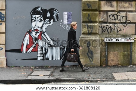 BRISTOL, UK - OCT 31, 2015: People pass graffiti on a building in the city centre. The west country city is famous for its vibrant graffiti and street art.