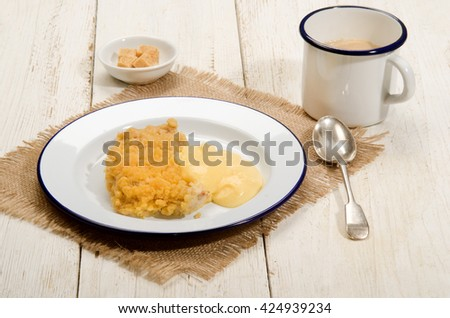 british apple crumble with custard on enamel plate, mug milk coffee and bowl with brown sugar cubes - stock photo