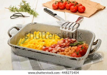 british breakfast with scrambled eggs in a roasting tin, smoked bacon cubes, baked beans, fresh tomatoes, rosemary   - stock photo