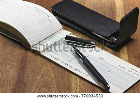 British checkbook on wooden desktop (account number is digitally altered and not real)  - stock photo