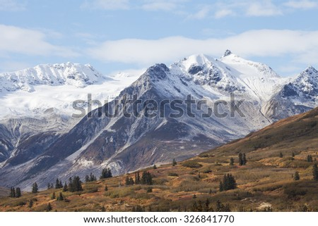 British Columbia's high mountains in fall with a dusting of early snow. - stock photo