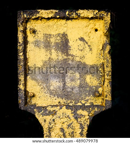 British concrete yellow fire hydrant with missing plate isolated on black.