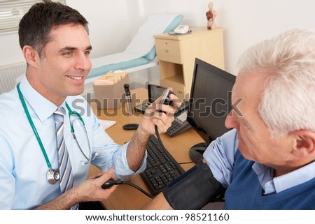 British doctor taking senior man's blood pressure - stock photo