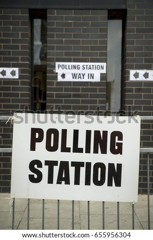British election polling station sign hanging on  fence in front of black brick wall in London, UK