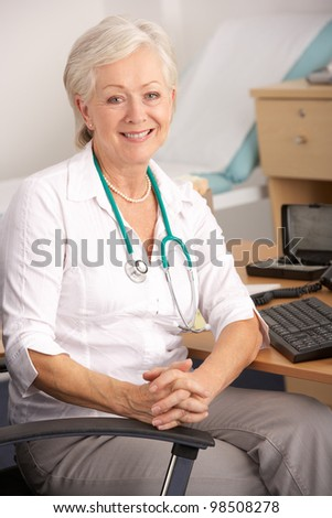 British female GP sitting at desk - stock photo