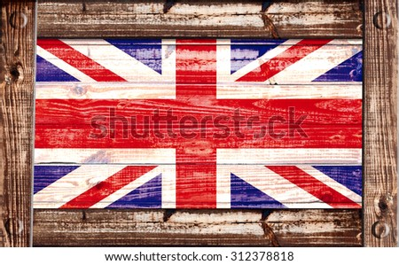 British flag on a grungy wooden textured background inside a wooden frame - stock photo